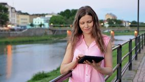 Pretty young girl using tablet computer near the railing on waterfront in evening time, old city, river and bridge in. The background stock video footage