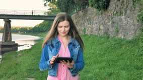 Pretty young girl walks along the waterfront and using tablet computer. Bridge and vintage wall of wild stone in the stock video