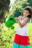 Pretty young girl watering flowers in the garden. Pretty young girl watering flowers in the garden with a bright green watering can wearing a pretty colorful royalty free stock photos