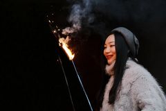 Asian chinese Girl holding sparkler firework with hand at black background . Brunette, looking Royalty Free Stock Images