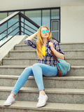 Pretty young girl wearing a checkered shirt, sunglasses with backpack Royalty Free Stock Photography