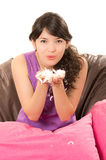 Pretty young girl wearing pajamas sitting with Royalty Free Stock Image