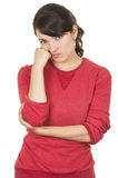 Pretty young girl wearing red top posing with hand. On cheek looking bored isolated on white royalty free stock images
