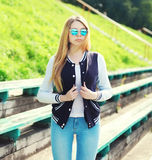 Pretty young girl wearing a sport jacket and sunglasses Royalty Free Stock Image