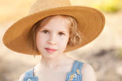 Pretty young girl wearing straw outdoors. Close up portrait of cute kid girl wearing hat outdoors Stock Image