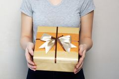 Pretty young girl wearing t shirt holding gift box with a bow royalty free stock photos