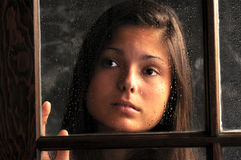 Pretty Young Girl in Window with Rain Drops Stock Images