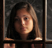 Pretty Young Girl in Window with Rain Drops Royalty Free Stock Photo
