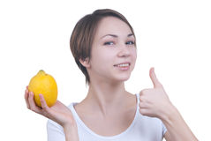 Pretty young girl with yellow lemon showing ok Royalty Free Stock Images