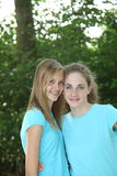 Pretty young girls in matching blue tops. Posing arm in arm with their heads close together in front of greenery in a park Stock Photos