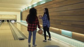 Girls invite cameraman to play bowling together. Pretty young girls are playing bowling in bowling club. Cute women invites cameraman to them to play game. Two stock footage