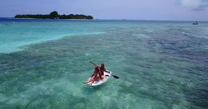 V08287 2 pretty young girls on a surfboard paddleboard with aerial view in warm blue sea water Royalty Free Stock Images