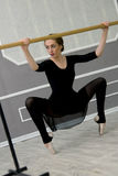 Pretty young graceful ballet dancer warms up in ballet class. Ballerina squats with his hands on the ballet barre stock photos