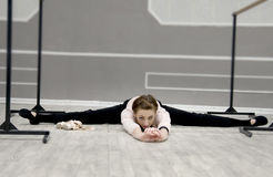 Pretty young graceful ballet dancer warms up. In ballet class Royalty Free Stock Image