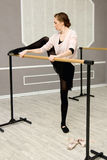 Pretty young graceful ballet dancer warms up. In ballet class Stock Image
