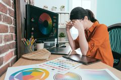 Pretty young graphic design company female staff. Sitting in front of working computer thinking when she designing new product having problem Stock Photo