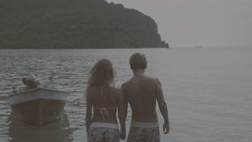 Pretty young happy couple holding hands and walking pier during their holiday with beautiful view of the sea and mountains ahead. Pretty young happy couple stock footage