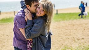 Pretty young happy couple hugging on the beach. Young happy couple hugging on the beach Stock Photo