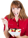 Pretty young happy redhead woman eating fruit salad Royalty Free Stock Photo