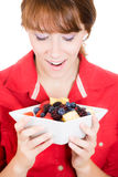 Pretty young happy redhead woman eating fruit salad Royalty Free Stock Images