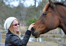 Pretty young happy woman outdoors with pet horse stroking him royalty free stock photos