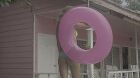 Pretty young happy woman wearing bikini and sunglasses walking with pink inflatable ring isolated on the background of pink house stock video footage