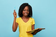 Pretty young hapy beautiful woman holding textbook and blue market notebook royalty free stock images
