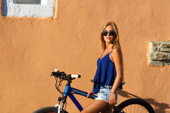 Pretty young hipster blonde girl posing with sport bicycle Stock Images