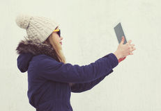 Pretty young hipster girl makes selfie on tablet pc outdoors Stock Photography