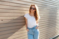 Pretty young hipster woman in stylish sunglasses in trendy white t-shirt in vintage jeans poses near a wooden wall. On a sunny summer day. Fashionable girl stock photos