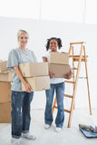 Pretty young housemates carrying moving boxes Royalty Free Stock Photo