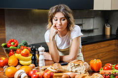 Pretty young housewife tired and sad in the kitchen Stock Image