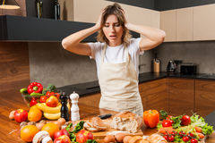 Pretty young housewife tired and sad in the kitchen Royalty Free Stock Photos