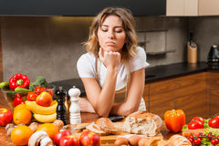 Pretty young housewife tired and sad in the kitchen Stock Images