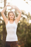 Pretty young jogger shaping heart with arms. In the nature stock photography