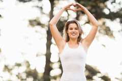 Pretty young jogger shaping heart with hands Royalty Free Stock Photography