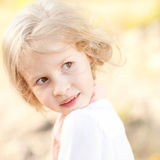 Pretty young kid girl posing outdoors. Closeup portrait of cute kid girl smiling outdoors Royalty Free Stock Photography