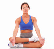 Pretty young lady doing lotus position. Pretty young lady in sport clothing doing lotus position on isolated background Stock Images
