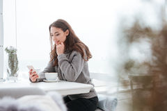 Pretty young lady drinking coffee while chatting by phone Stock Photography