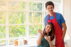 Pretty young lady eating  cereals with her boyfriend next to big glass window royalty free stock photo