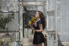 Pretty young lady holding a bouquet of flowers royalty free stock photo