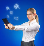 Pretty young lady looking at social media icons Stock Photo