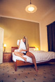Pretty young lady in love sitting on the bed and plays with a pillow. Royalty Free Stock Photography