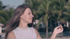 Pretty young lady with manicure and loose hair slow motion. Pretty young lady with stylish manicure and long loose hair poses on tropical resort close view slow stock video