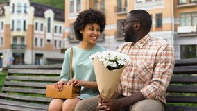 Pretty young lady meeting boyfriend on first date, man presenting white flowers