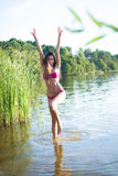 Pretty young lady in pink swimwear jumping with Stock Photo