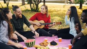 Pretty young lady is playing guitar while her friends are singing and listening to music resting on plaid in park. Food royalty free stock photo