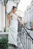 Pretty young lady. Posing on the street near the handrail standing on the steps dressed in a long dress stock photo
