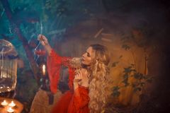 Pretty young lady preparing a potion to bewitch her beloved boyfriend, girl with blond curly hair in a long sexy red stock photos
