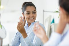 Pretty young lady putting on earrings in front mirror stock image